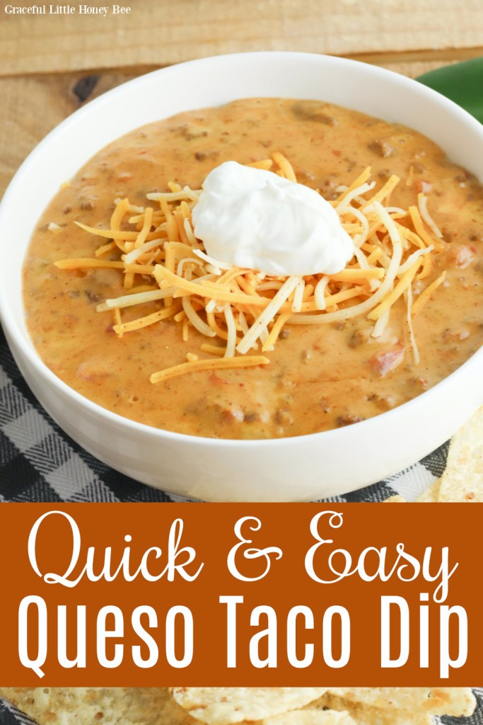Queso Taco Dip in a white bowl topped with shredded cheese and sour cream.