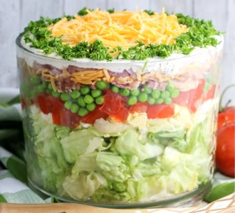 7-Layer Salad in a clear glass trifle bowl sitting on a marble counter with a wooden spoon sitting next to it.