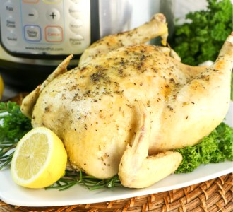 Whole Lemon Garlic Chicken sitting on a white platter garnished with parsley and lemon.