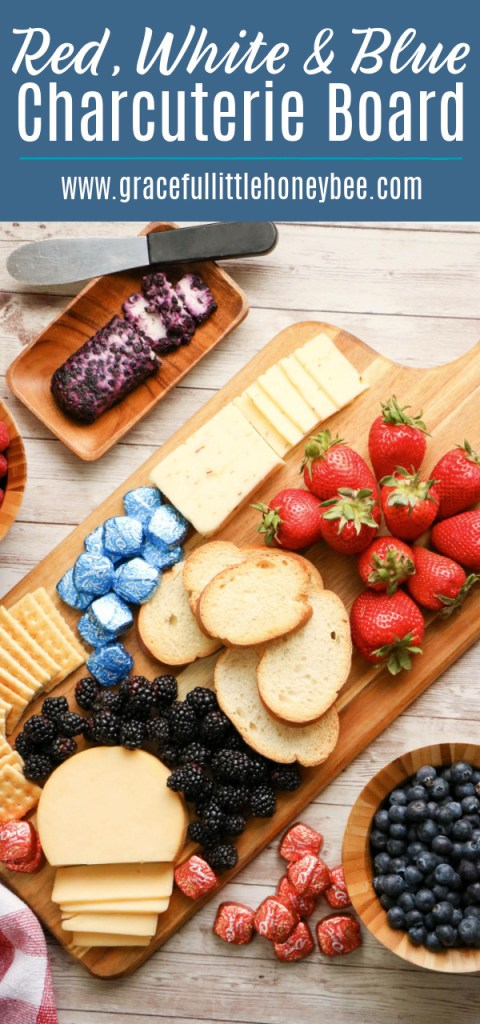An assortment of red, white and blue finger food arranged neatly on a cutting board including strawberries, blueberries, crackers, cheese and chocolate.