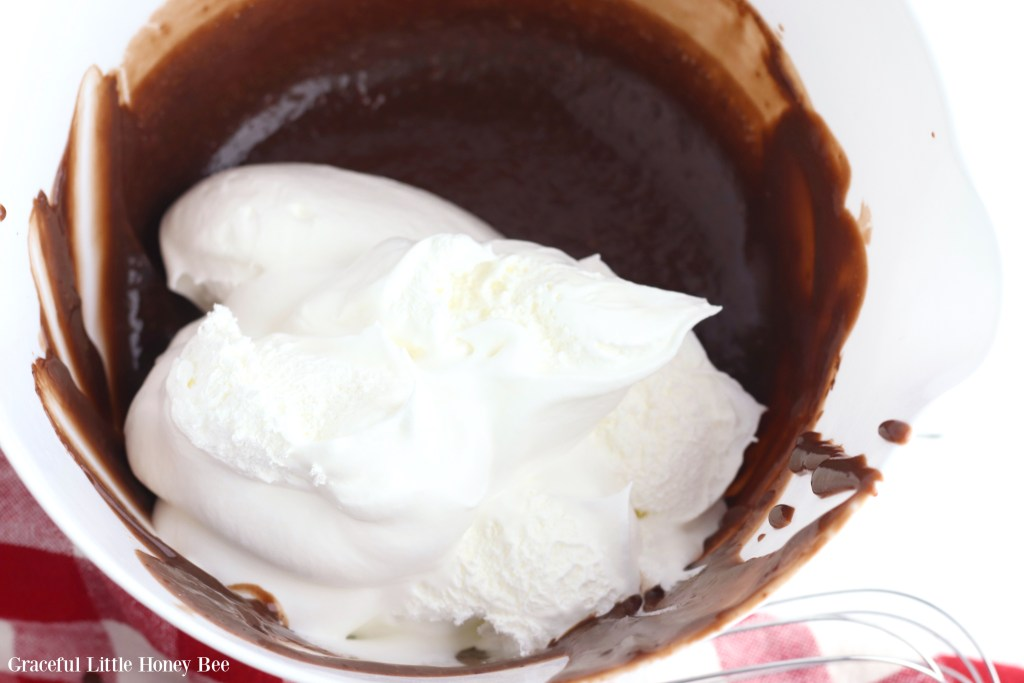 Chocolate pudding and whipped topping in a mixing bowl before being stirred together.