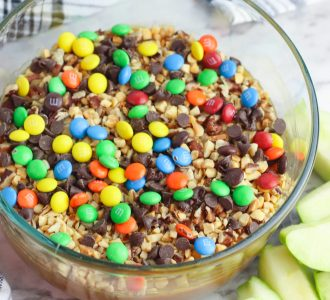 Caramel Apple dip with Peanuts and Chocolate Candy in a clear glass bowl with green apple slices sitting next to it.