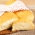 French Bread sitting on a mat with a slice in front and a tea towel laying over the top.