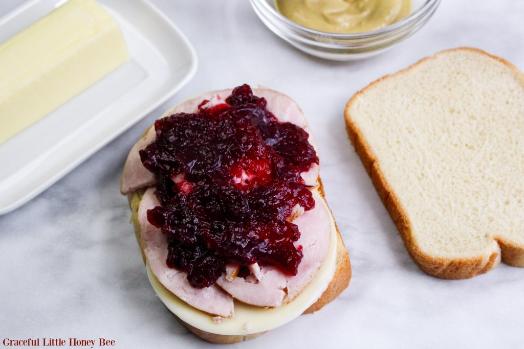 Open faced sandwich with mustard, cheese, turkey and cranberry sauce before being grilled.