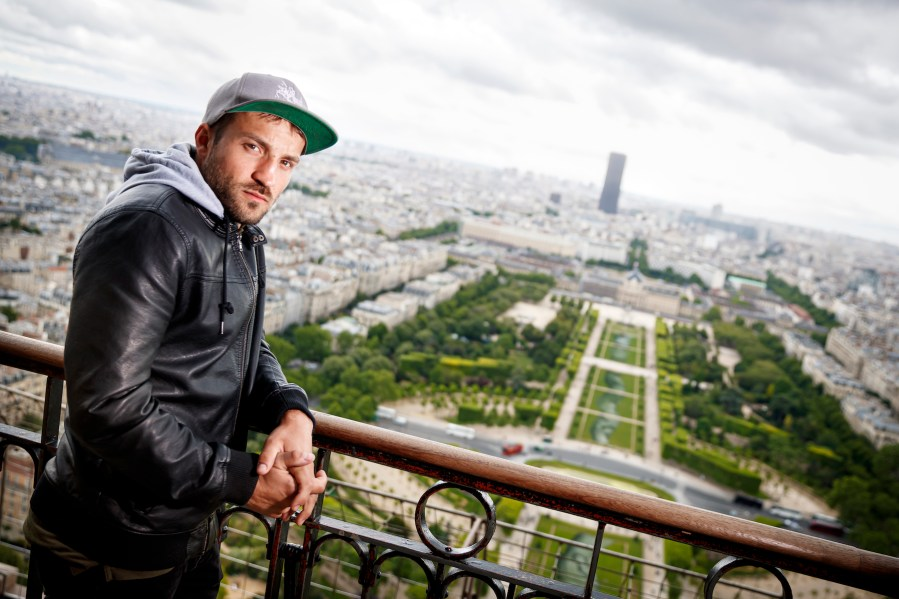 "French-Swiss artist Saype poses in front of his giant biodegradable landart painting on Tuesday June 11, 2019 on the Champ de Mars in front of the iconic Eiffel Tower in Paris, France. With an overall area of 15'000 square meters, the 600 meters long and 25 meters wide painting (likely one of the largest of its kind) was created using biodegradable pigments made out of charcoal, chalk, water and milk proteins. This art piece launches the worldwide project ""Beyond Walls"" aiming at creating the longest symbolic human chain around the world promoting values such as togetherness, kindness and openness to the world. (VFLPIX.COM /Valentin Flauraud)"