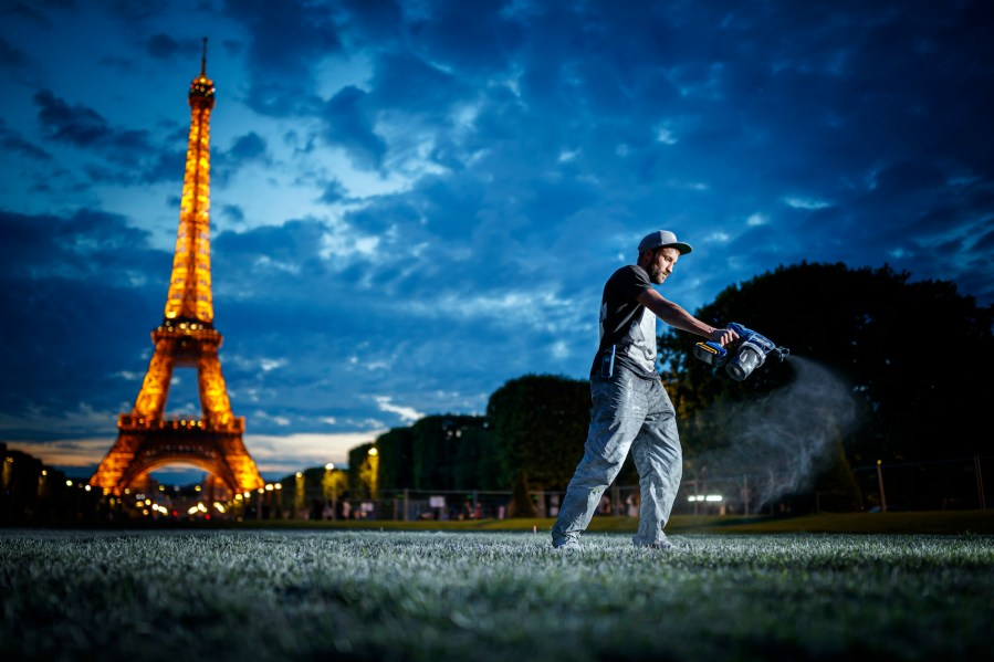"""Giant biodegradable landart painting by French-Swiss artist Saype, picture taken between June 9 and 12, 2019 on the Champ de Mars in front of the iconic Eiffel Tower in Paris, France. With an overall area of 15'000 square meters, the 600 meter long and 25 meter wide painting (likely one of the largest of it's kind) was created using biodegradable pigments made out of charcoal, chalk, water and milk proteins. This art piece launches the worldwide project """"Beyond Walls"""" aiming at creating the longest symbolic human chain around the world promoting values such as togetherness, kindness and openness to the world. (VFLPIX.COM /Valentin Flauraud)"""
