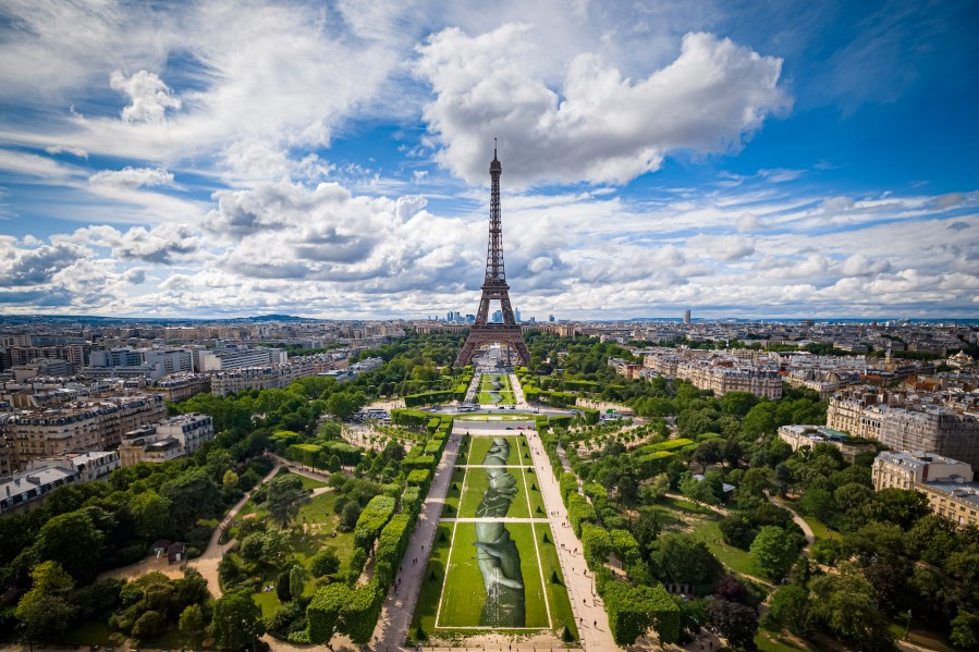 """A giant biodegradable landart painting by French-Swiss artist Saype is pictured Monday June 10, 2019 on the Champ de Mars in front of the iconic Eiffel Tower in Paris, France. With an overall area of 15'000 square meters, the 600 meters long and 25 meters wide painting (likely one of the largest of its kind) was created using biodegradable pigments made out of charcoal, chalk, water and milk proteins. This art piece launches the worldwide project """"Beyond Walls"""" aiming at creating the longest symbolic human chain around the world promoting values such as togetherness, kindness and openness to the world. (VFLPIX.COM /Valentin Flauraud)"""