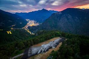"""A giant biodegradable landart painting by French-Swiss artist Saype is pictured between July 15 and July 16, 2019 at Engolasters in Andorra. With an overall area of 5'000 square meters, the 130 meters long and 38 meters wide painting was created using biodegradable pigments made out of charcoal, chalk, water and milk proteins. This art piece is the second step of the worldwide """"Beyond Walls Project"""" aiming at creating the longest symbolic human chain around the world promoting values such as togetherness, kindness and openness to the world. (VFLPIX.COM /Valentin Flauraud)"""