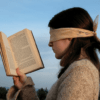 Woman trying to read book whilst blindfolded