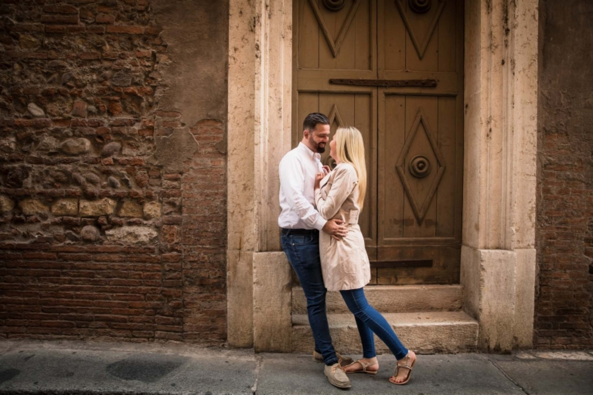 A romantic couple hug one another in Verona, Italy