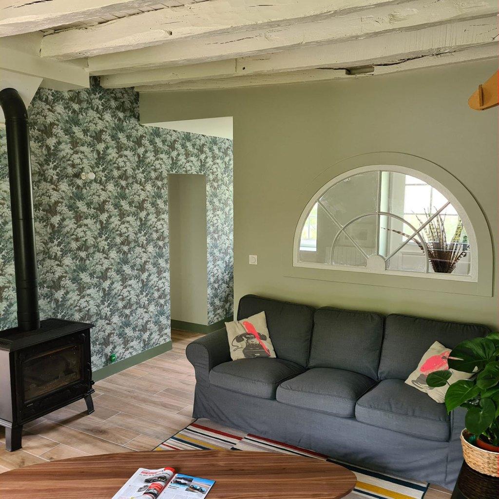 La Maison de Célestin, salon avec canapé moelleux et table en noyer ovale. Poêle à bois en fonte