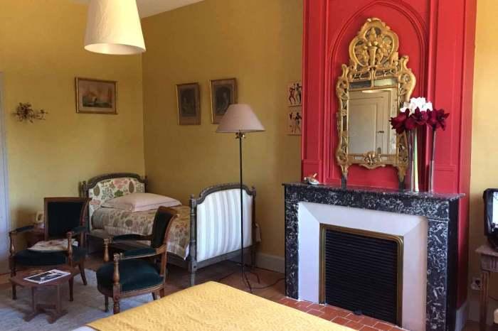 La chambre Amédée de Grand Bouy, pour 3 personnes vue sur la cheminée surmontée d'un miroir de Beaucaire.