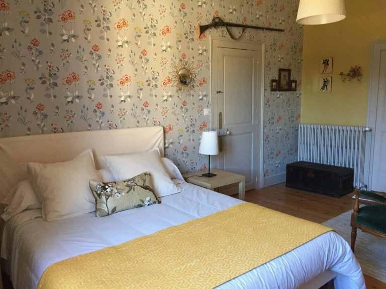 La chambre Amédée de Grand Bouy, vue depuis la fenêtre, derrière le lit Queen size, un mur en papier peint Willowbrook de Jane Churchill