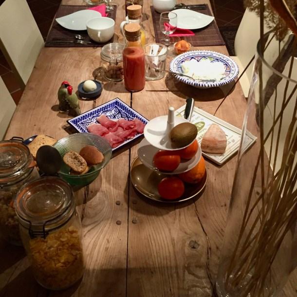 Table de ferme en bois avec petit-déjeuner de produits locaux, jus de fruits, fruits frais, jambon, fromage de chèvre, pétales de céréales, pain maison