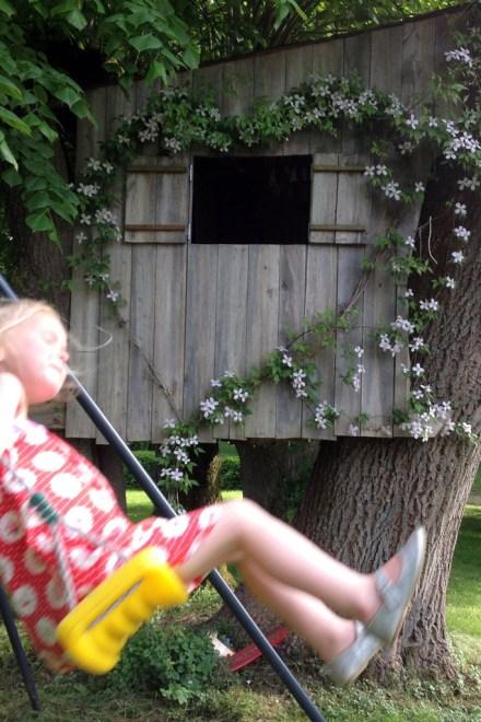 Dans le parc de Grand Bouy, une fillette fait de la balançoire devant une cabane dans les arbres ornée d'une clématite Montana