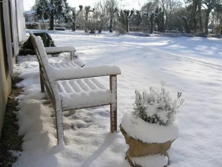 Banc à lames en bois et pot de lavande sous la neige
