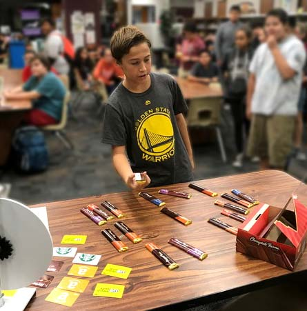 A student selects candy from a table spread with candy bars