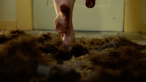 A pair of bare feet standing in a pile of hair