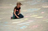 Photo of student drawing with sidewalk chalk