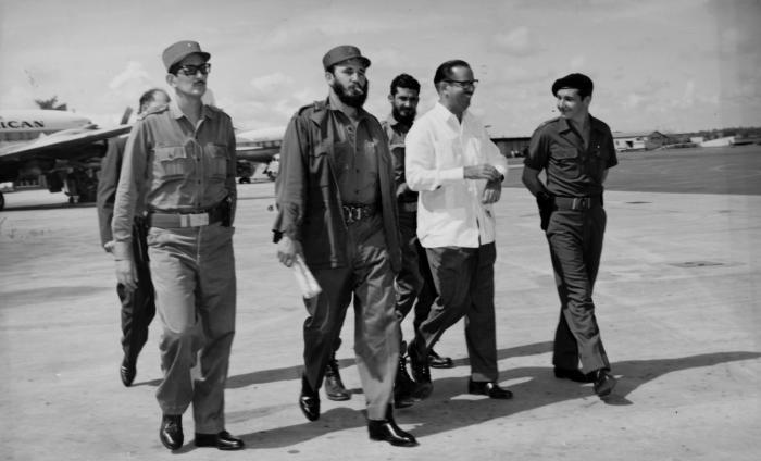 Fidel Castro camina hacia el avión que lo conducirá a él y a la delegación cubana que participará en el XV Periodo de Sesiones de la Asamblea General de la ONU en Nueva York. Lo acompañan el Comandante Raúl Castro, el presidente Osvaldo Dorticós y el Comandante Julio Camacho Aguilera, y el Comandante Augusto Martinez Sánchez (detrás en la foto) .