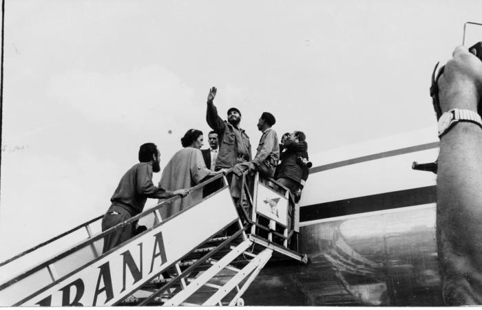 Fidel saluda desde la escalerilla del avión que lo conducirá a él y a la delegación cubana que participará en el XV Periodo de Sesiones de la Asamblea General de la ONU en Nueva York. Celia Sánchez y Antonio Núñez Jiménez lo acompañan.