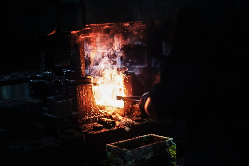 Blacksmith inserting axe head into forge fire