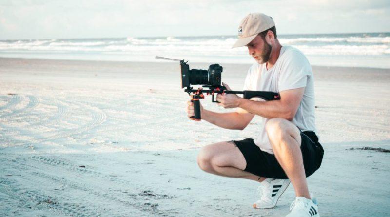 man holding black dslr camera outdoors