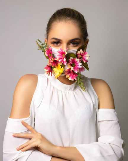 serious haughty woman in mask with flowers