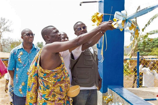 Mr Kwaku Tweneboah Ofosu (right) being assisted by Abusuapanyin Ofori (in cloth), chief of Asasekorkor, to cut the tape to inaugurate the mechanised borehole. Looking on is Mr Carlos Arko (extreme left), the project manager