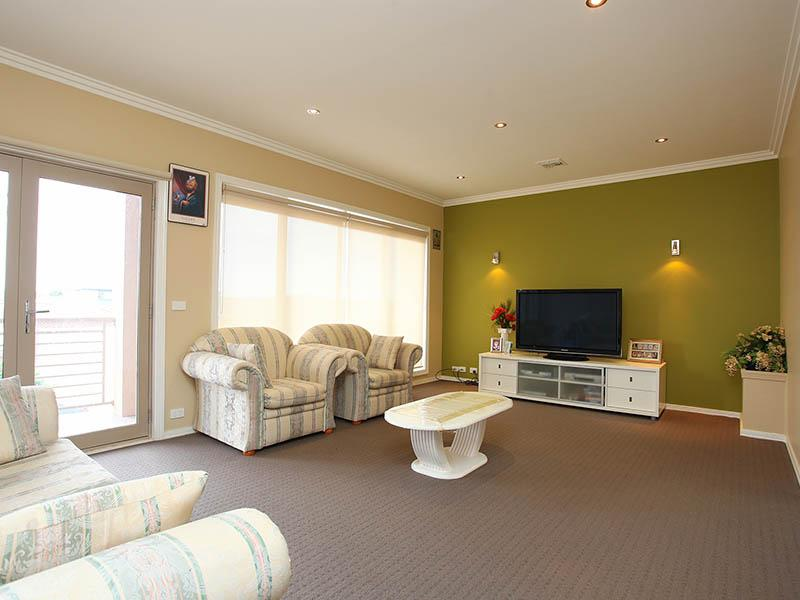 Spacious room with orange wall paint and comfy sofa also flowers decor