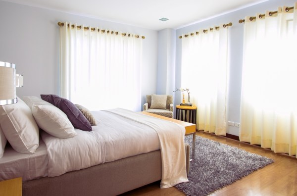 inspiring bedroom with white bed comforter and corner chair and sleek curtains also wooden floor decor ideas