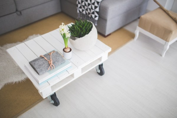 white pallet as coffee table with wheels and grey sofa view at bright room