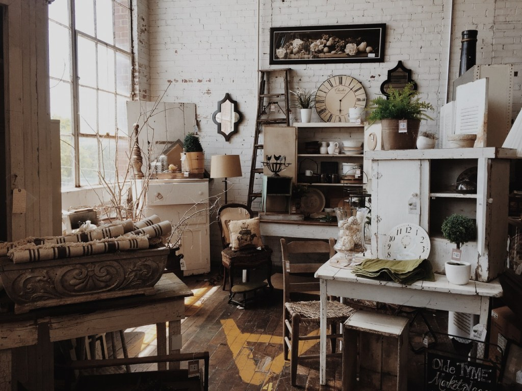 brown wooden chair near white wooden table with white cabinet on top also brick wall