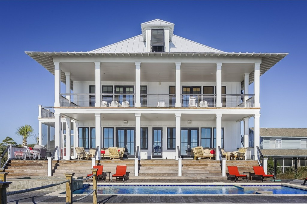 luxury large home with pool and pillars also outdoor chairs