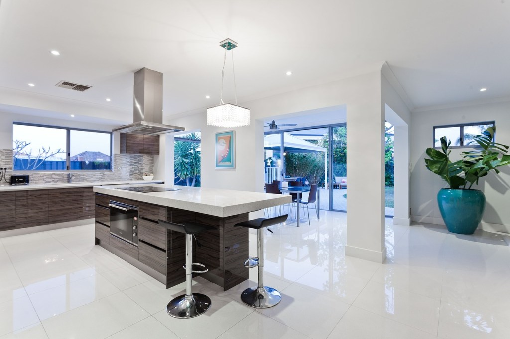modern kitchen with stools and hood also good lighting