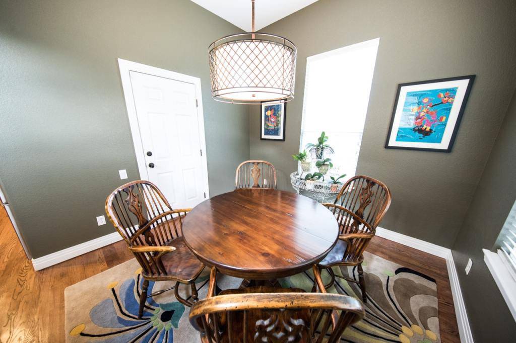 brown wooden dining set with pendant lamps and wall art also wooden floor