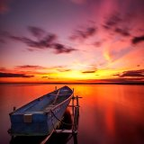 Floating boat at sunset