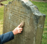 Carefully cleaning a gravestone