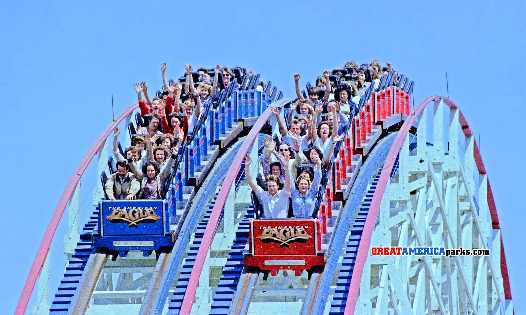 American Eagle blue and red trains crest the lift hill.
