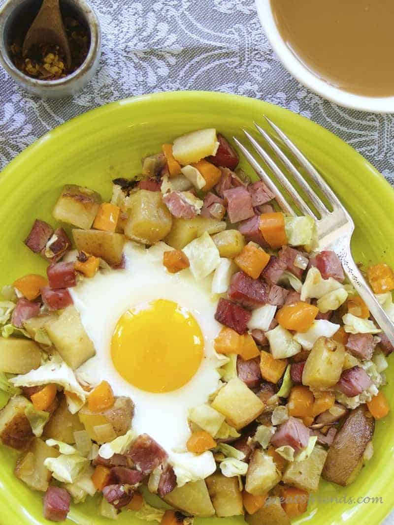 Overhead shot of hash on a plate with an egg and a cup of coffee.