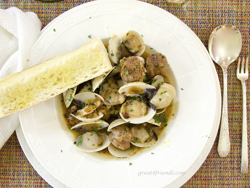 Overhead shot of Clams with Hot Italian Sausage in bowl with bread and spoon