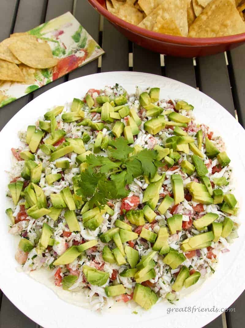 Overhead shot of Layered Crab Dip topped with diced avocado and cilantro.