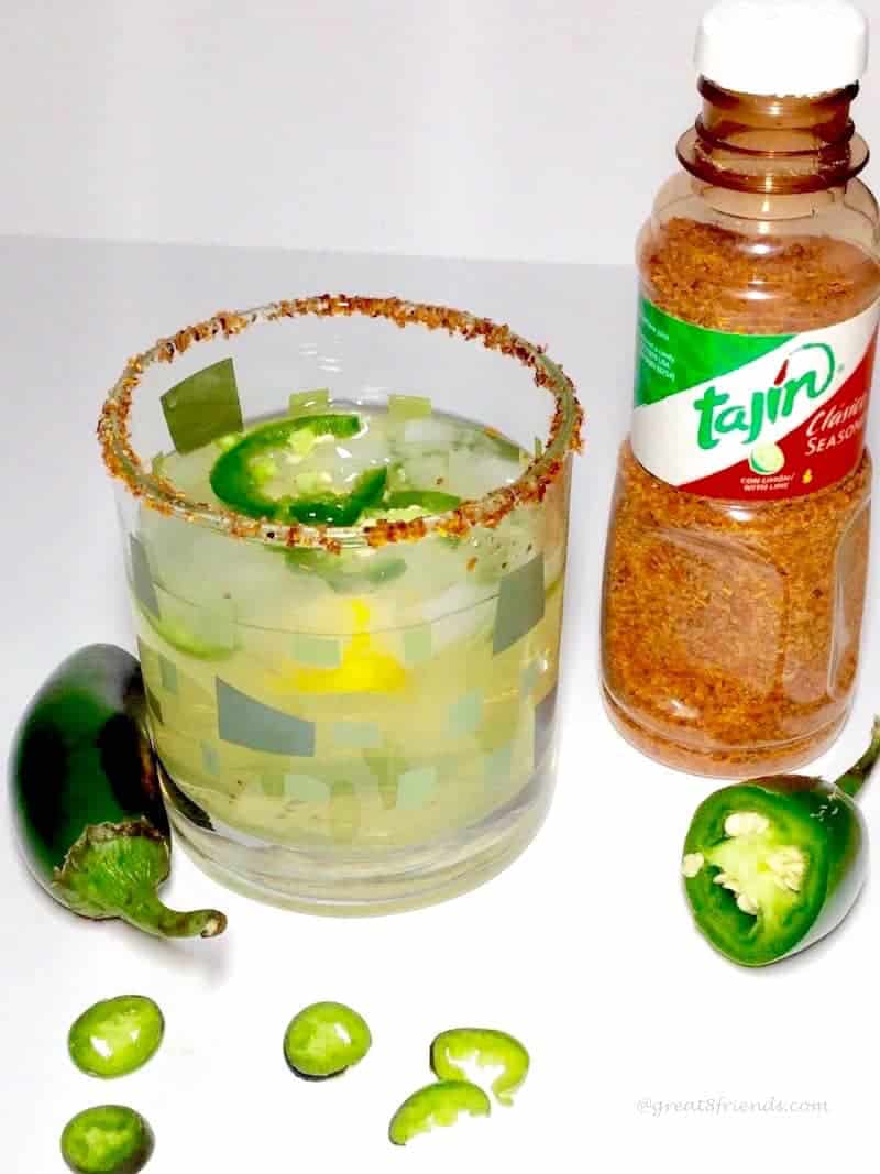 Margarita with a jalapeño slices and Tajin seasoning on the rim of the glass.