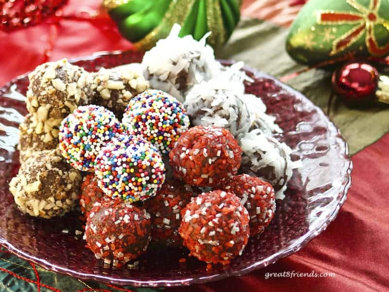 Chocolate truffles on red glass plate with Christmas decorations.