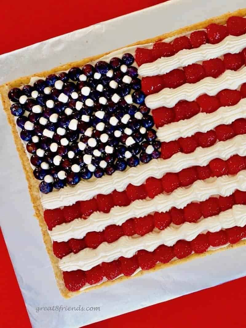 Overhead view of an American Flag Fruit Pizza made with a cookie crust, cheesecake mousse for the stripes and stars and raspberries as the red stripes and blueberries.
