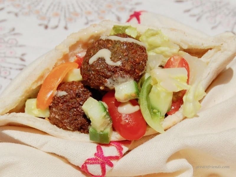 An unclose view of falafels stuffed in a pita bread with chopped fresh cucumbers and tomatoes and tahini.