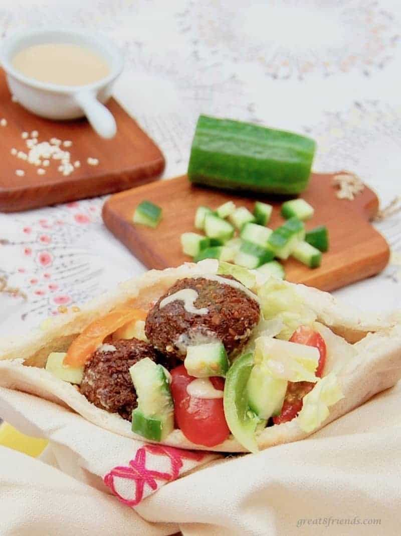 A Falafels served in a pita with chopped cucumber and tomatoes with tahini on the side.