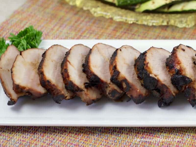 Side view of a sliced pork tenderloin with a parsley garnish.