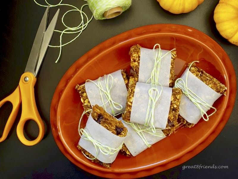 Pumpkin Granola Bars wrapped in parchment and stacked on an orange plate.