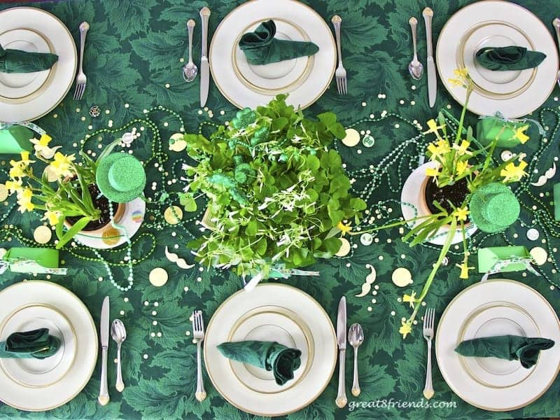 Overhead shot of table set for St. Patrick's Day, white china with gold rim, on green tablecloth with shamrock and daffodil centerpieces and green and gold beads and coins.